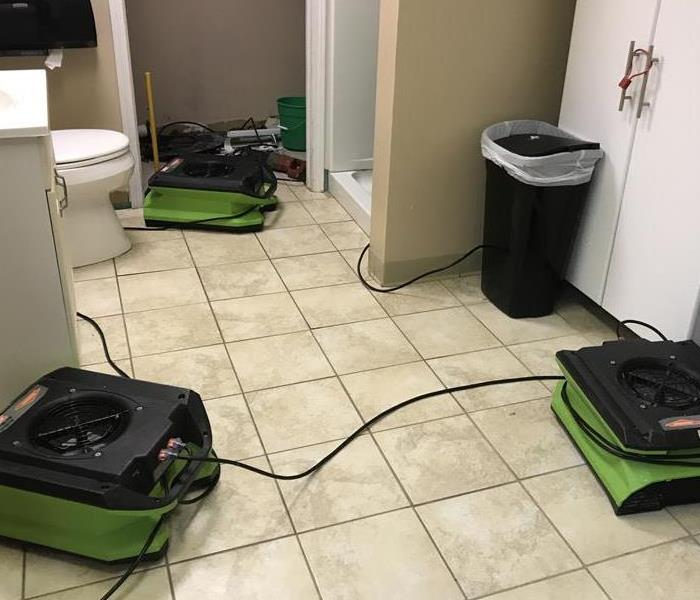 Green air movers and scrubbers on tile floor in bathroom
