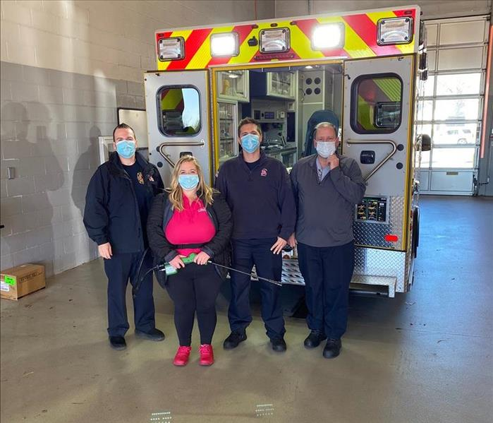 Four people in masks standing in front of a fire truck.