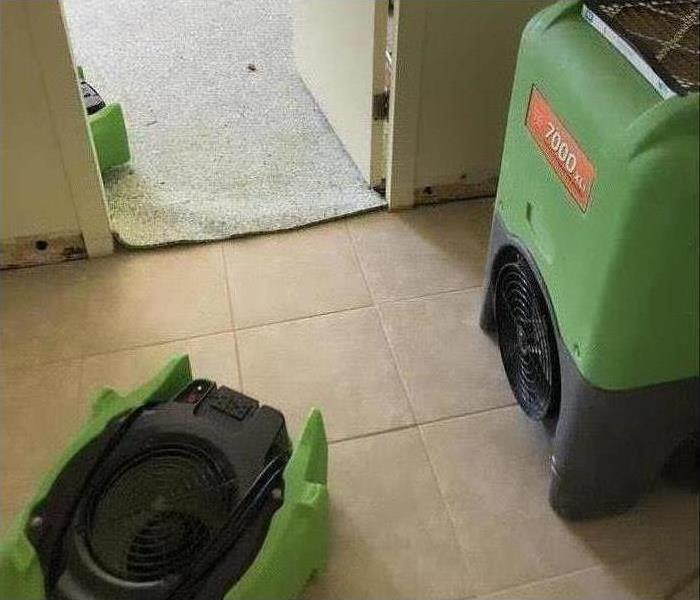 Air mover and a humidifier placed on a floor, drying up damaged area