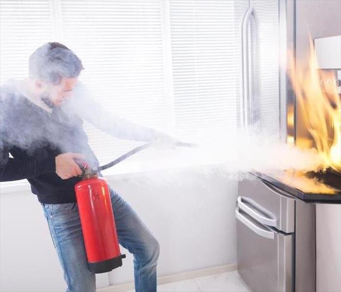 Man using a red fire extinguisher to stop fire coming from oven in kitchen