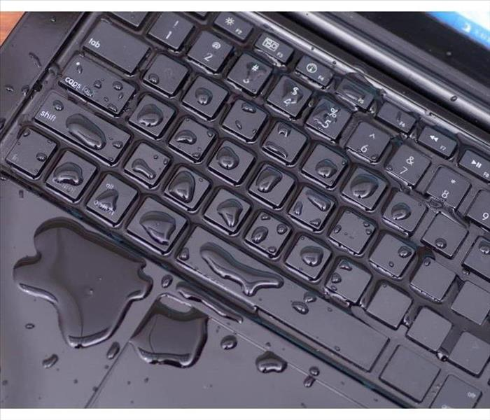 Above view of laptop with water drop damage liquid wet and spill on keyboard, accident concept