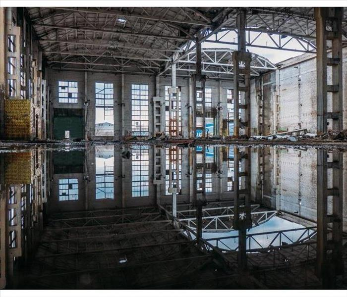 Inside of flooded dirty abandoned ruined industrial building with sewage water in the interior.